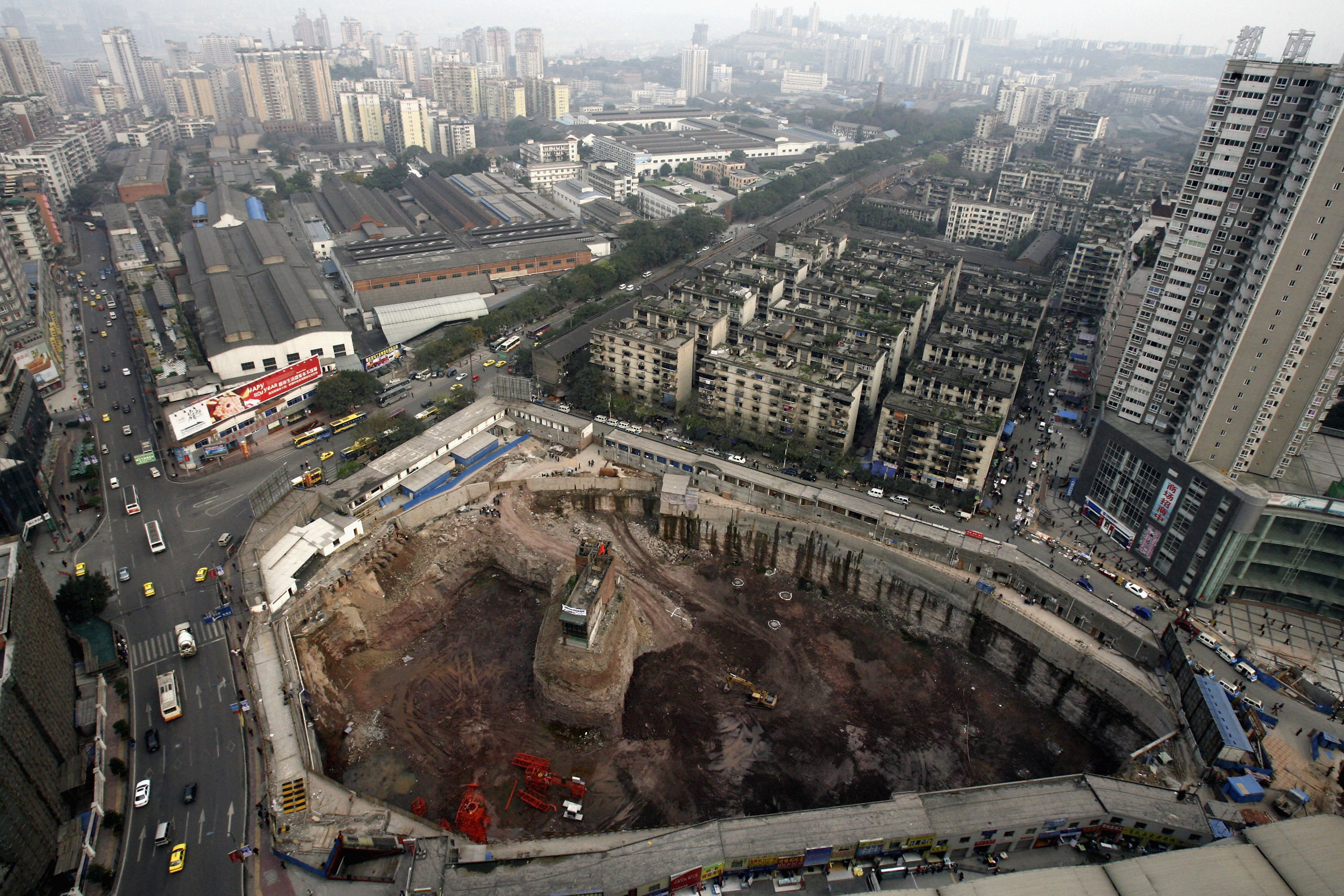 CHONGQING, CHINA - MARCH 22: (CHINA OUT) A building sits on its own island of land amid construction all around it, on March 22, 2007 in Chongqing Municipality, China. The homeowner, who has hung a banner and the national flag in protest, has refused to sell to a developer who went ahead with construction around the site. The Jiulongpo District Court has ordered the household to move out before March 22. The National People's Congress, China's legislature, just approved a much-debated new property law that for the first itme provides legal protections for private assets in China. (Photo by China Photos/Getty Images)