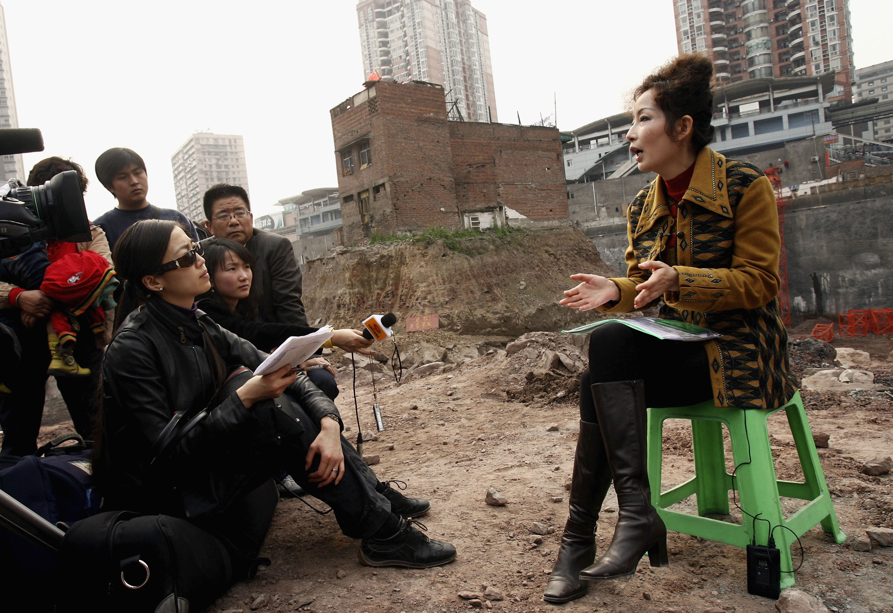 CHONGQING, CHINA - MARCH 22: (CHINA OUT) Wu Ping (R), the owner of a building sitting on its own island of land amid construction all around it, answers reporters' questions March 22, 2007 in Chongqing Municipality, China. The homeowner, who has hung a banner and the national flag in protest, has refused to sell to a developer who went ahead with construction around the site. The Jiulongpo District Court has ordered the household to move out before March 22. The National People's Congress, China's legislature, just approved a much-debated new property law that for the first itme provides legal protections for private assets in China. (Photo by China Photos/Getty Images)